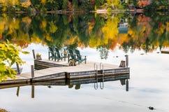 Reihe von grünen Adirondack-Stühlen auf einer Anlegestelle Stockfotografie