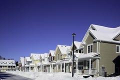 Reihe von Häusern mit Schnee auf Dächern und an der Front Stockbilder