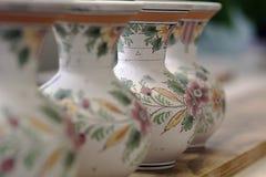 Reihe von handgemalten weißen Delft-Tonwarenvasen mit Blumendetails in Holland Stockfoto