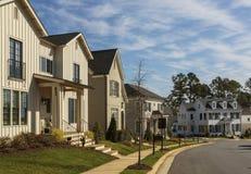 Reihe von hochwertigen Familienhäusern auf einer gebogenen Nachbarschaftsstraße Stockfotos