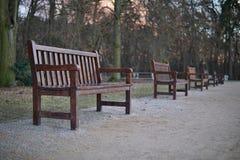 Reihe von Holzbanken im Park als Symbol der Entspannung und des Habens eines Restes Stockbilder