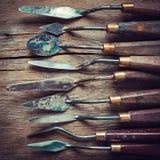 Reihe von Künstlerpalettenmessern auf altem Holztisch Stockfoto