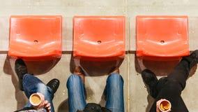 Reihe von Plastikstühlen und von Beinen im Fußballstadion Lizenzfreies Stockfoto