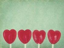 Reihe von roten Lutscherherzen auf Weinlesehintergrund Lizenzfreies Stockfoto