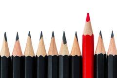 Reihe von schwarzen Bleistiften mit einem roten Bleistift in der Mitte Stockbilder