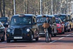 Reihe von schwarzen London-Fahrerhäusern in einem Verkehrshalt mit einem weiblichen Radfahrer Stockbilder