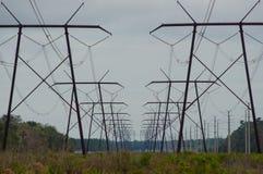 Reihe von Starkstromleitungstürmen in der Perspektive stockfotos