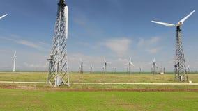 Reihe von Türmen mit Windkraftanlagen im Hintergrund des blauen Himmels stock video footage