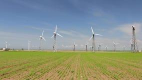Reihe von Türmen mit Windkraftanlagen im Hintergrund des blauen Himmels stock footage
