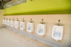 Reihe von Toilettentoilettenblöcken für Toilette der Mannfliesenwand öffentlich stockbild