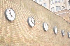 Reihe von Uhren auf einer hohen Backsteinmauer Stockfotografie