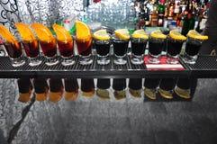 Reihe von vier Getränken schwarzem Wodka auf dem Stab lizenzfreie stockfotos
