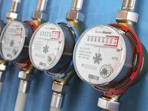 Reihe von Wasserzählern kaltem und Heißwasser auf dem Wandhintergrund Lizenzfreies Stockfoto