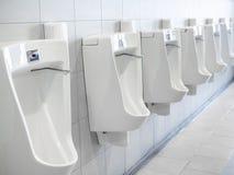 Reihe von weißen Toiletten in der Manntoilette lizenzfreie stockfotos