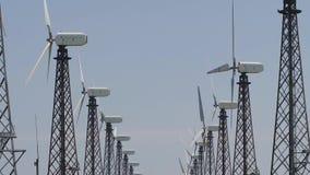 Reihe von Windkraftanlagetürmen im Hintergrund des blauen Himmels stock video