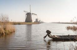 Reihe von Windmühlen und von kleinen Boot Stockfotos