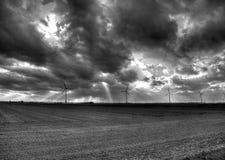Reihe von windturbines unter einem drastischen Himmel Stockbild