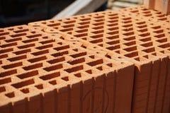 Reihe von Ziegelsteinen in der roten Farbe mit den inneren Löchern in Form der Bienenwabe auf der Baustelle Stockbild