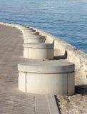 Reihe zementierte Bänke entlang dem Meer Stockfotos