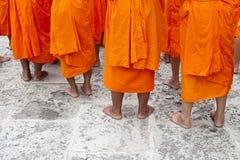 Reihen der jungen siamesischen buddhistischen Anfängermönch-Stellung Stockfoto