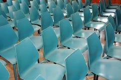 Reihen der kleinen blauen Stühle Lizenzfreie Stockfotos