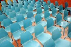 Reihen der kleinen blauen Stühle Stockbild
