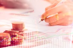 Reihen der Münze und des Geschäftsmannes bezüglich des Kontrolldiagramms der Börse handeln Lizenzfreies Stockfoto