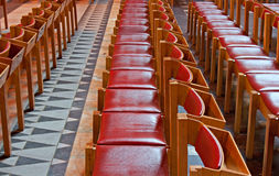 Reihen der roten hölzernen Stühle in der Kirche Stockbild