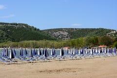 Reihen des gestreiften Regenschirmes auf einem Meer setzen auf den Strand Stockfoto