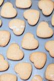 Reihen des Herzens formten Kekse auf Metallbackblech Lizenzfreie Stockfotos