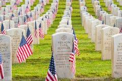 Reihen-Veteranen-ernste Markierungen mit amerikanischen Flaggen Stockfotografie