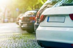 Reihen von Autos parkten auf dem Straßenrand im Wohnviertel lizenzfreie stockfotos