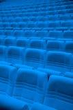 Reihen von blauen Lehnsesseln in der leeren Halle Stockfotografie