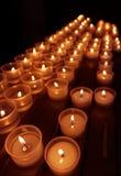 Reihen von brennenden Kerzen in einer Kirche Stockbild