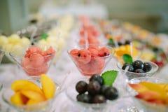 Reihen von Cocktailgläsern mit frischen Sommerfrüchten und -beeren Stockbilder