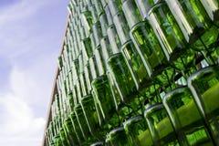 Reihen von den grünen leeren Flaschen, die an den Nägeln mit blauem Himmel hängen Stockfoto