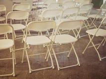 Reihen von den leeren Stuhlsitzen installiert für Parteiereignis im Freien Stockfoto