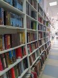 Reihen von den verschiedenen bunten Büchern, die auf den Regalen in der modernen Buchhandlung liegen stockfoto