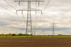 Reihen von Energiemasten in einer ländlichen Landschaft Stockfotografie