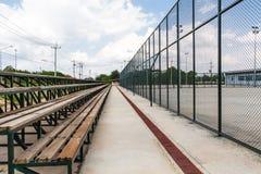 Reihen von leeren Sitzen der hölzernen Haupttribüne des Tennisfeldes Stockfotografie