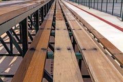 Reihen von leeren Sitzen der hölzernen Haupttribüne des Tennisfeldes Stockbilder