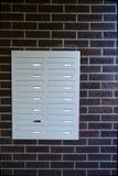 Reihen von modernes Metallgrauen Briefkästen auf einer Backsteinmauer lizenzfreie stockfotos