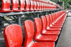 Reihen von roten Minifußballstadionssitzen stockbilder