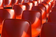 Reihen von roten Plastikstühlen Lizenzfreies Stockfoto