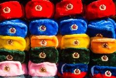 Reihen von russischen Winterhüten von verschiedenen Farben mit Armeeemblemen am Straßenmarkt an alter Arbat-Straße Lizenzfreie Stockfotos