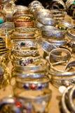 Reihen von silbernen Armbändern auf Gold Stockfotografie
