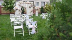 Reihen von Stühlen an einer Hochzeitszeremonie Hochzeits-Blumen-Bogen-Dekoration Hochzeitsbogen verziert mit Blumen outdoor stock video footage