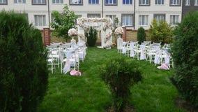 Reihen von Stühlen an einer Hochzeitszeremonie Hochzeits-Blumen-Bogen-Dekoration Hochzeitsbogen verziert mit Blumen outdoor stock footage