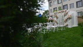 Reihen von Stühlen an einer Hochzeitszeremonie Hochzeits-Blumen-Bogen-Dekoration Hochzeitsbogen verziert mit Blumen outdoor stock video