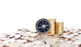 Reihen von Stapelmünzen und -kompaß Stockfoto
